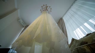 Elegant white wedding dress hanging in the room.