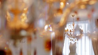 Elegant white wedding dress hanging on a crystal chandelier.