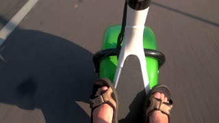 Fat wheel scooter is moving. Guy's feet in sandals. Transport based on modern technologies.
