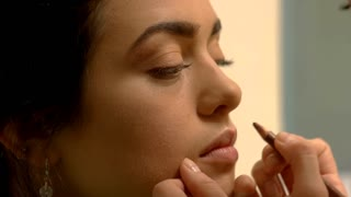 Female hand applying makeup. Face of a young woman. Visagist busy at work. Add more color.
