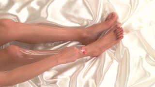 Female hand is shaving leg. Legs on white silk cloth. Make skin smooth and soft. Foam and razor.