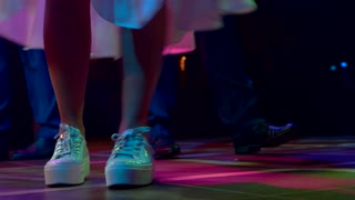 Female legs dancing. Woman's feet in white sneakers. Party all night long. Steps and turns.