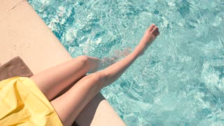 Female legs in swimming pool. Top view of clear water. Forget problems and enjoy summer.