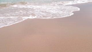 Foamy water and sand. Seashore at daytime. Island amidst sea.