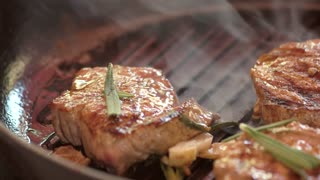 Frying pan with meat pieces. Grilled steaks and rosemary. Try new recipe of veal.
