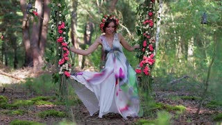 Gentle forest fairy on a swing of roses.