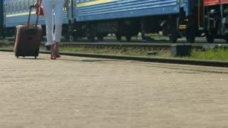 Girl goes on the platform. Girl traveling.
