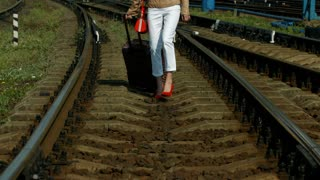 Girl in red shoes walking on the rails. Girl traveling.
