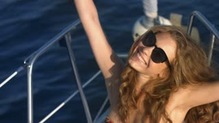 Girl sitting on board the yacht. Vacation on a yacht. Cruise on the ship. Journey across the ocean.