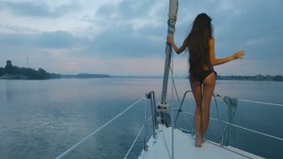 Girl with long hair enjoying a cruise on a sailing yacht. Night walk on the yacht along the river. Rest on the yacht. Travel by sea.