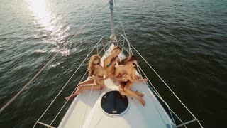 Girlfriends rest on the sea. Girls enjoy the vacation on a yacht. Tourists sunbathing on the yacht. Party on a yacht. Corporate party on a yacht.
