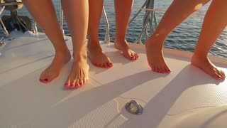 Girls dancing on board. Relax on a cruise ship. Legs of girls close-up. Leisure at sea. Walk on a yacht.