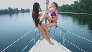 Girls relaxing on a yacht. Girlfriends traveling on the lake by boat. The girls are drinking juice and talking on the boat.