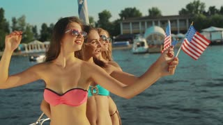 Girls resting on the sea. American girls.  Girls patriotic with American flags. Girls waving the American flags. Models with American flags.