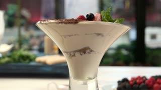 Glass filled with dessert. White cream and berries. Tiramisu in Italian cafe.