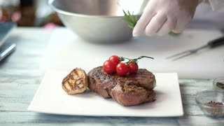 Grilled meat with vegetables. Hand of chef decorating food. Steak presentation ideas.