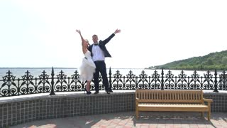 Groom and bride waving hands. Wedding couple near water. Love wider than horizon. Start of new happy life.