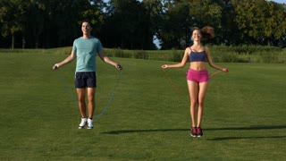 Guy and girl are jumping on the jump rope. Sport youth. Guy and girl are engaged in a warm-up outdoors.