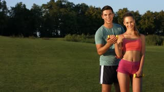 Guy and girl engaged in sports on a golf course. Happy young people involved in sports. Guy train a girl in the park.