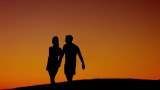 Guy and girl holding hands. Loving couple walk along evening mountains. Beautiful sunset in the mountains. Love story. Honeymoon.