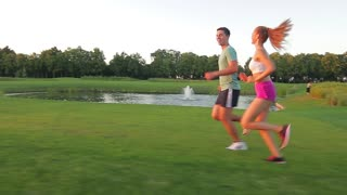 Guy and girl run through the beautiful nature reserve. Healthy lifestyle. Athletics. Evening jogging outdoors.