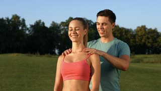 Guy makes a massage for girl on nature. Relax outdoors. Fitness trainer kneads muscles of girl.