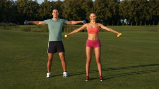 Guy with girl engaged in fitness in a beautiful park. Sport life. Sports activities on the nature.