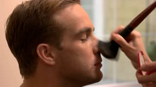 Hand applying makeup on man. Side view of male face. Visagist working with a model. Actor before shooting.