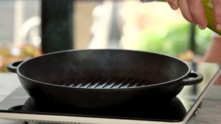 Hand pours oil in pan. Frying pan on stove.