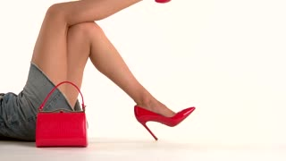 Handbag and woman's legs. Red heels and purse. How to dress sexy. Expensive footwear for ladies.