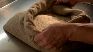 Hands and sack with rice. Palm holding groats. Best grain supplier.