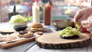 Hands preparing cheeseburger. Wood board and burger. Fast food sandwich recipes.