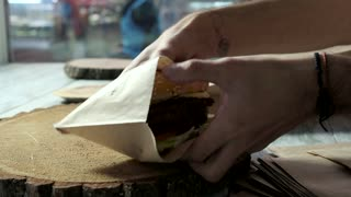 Hands putting burgers into bag. Man packing food indoor. Meal deals in american cafe.
