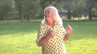 Happy woman dancing. Smiling elderly lady outdoor. Small joys every day. Save positive mood.