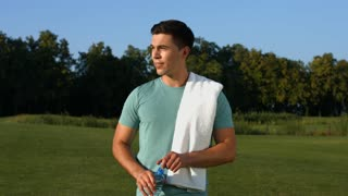 Healthy lifestyle. Beautiful sportsman drinking water on the lawn. Sportsman outdoors. Handsome guy on a green meadow.
