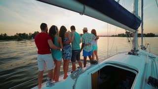 Holiday on a sailing yacht. Loving couples relaxing on a yacht. Guys and girls on a sea voyage on a sailing yacht. Young people spend a weekend on a yacht at sunset.