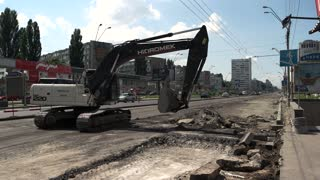 Kiev, Ukraine - 27. 07. 2016. Digger on road. Part of work is done. Building company restores roads.