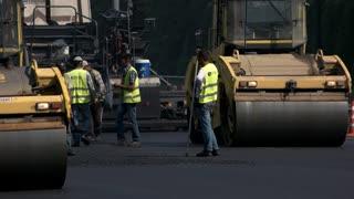 Kiev, Ukraine - 27. 07. 2016. Men with shovels throwing asphalt. Thorough roadway repairs. Working in a team.