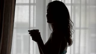 Lady with cup in slow-mo. Silhouette of girl near window. Every morning starts from coffee. Need a rush of energy.