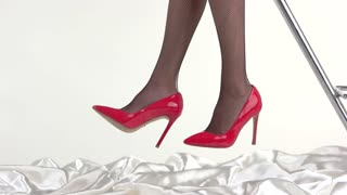 Legs wearing fishnets and heels. Red shoes with black tights. Draw attention of any man. Hypnosis by beauty.