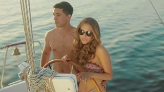 Love story. Loving young couple relaxing on a yacht. Just Married traveling on a yacht. Guy and a girl went to a sea voyage on a yacht. Summer vacation on a yacht.