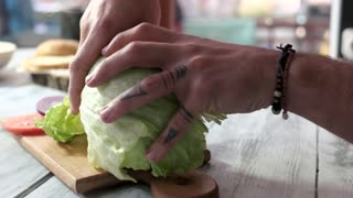 Male hands breaking lettuce. Vegetable pieces on wood board. Vegetarian cooking ideas.