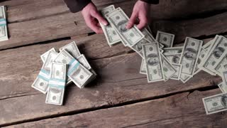 Male hands counting american dollars. Money on old wooden background. Time to count the savings. Piles and bundles.