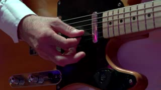 Male hands playing electric guitar. Man with a musical instrument. Riffs and chords. Guitarist of rock-n-roll band.