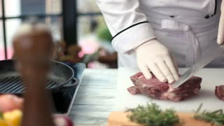 Meat and knife in hands. Cooking board with raw steak. Chef is busy at work.