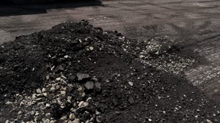 Milled asphalt pile. Small rocks on the ground. City roads will be reconstructed. Destroy and build.