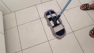 Mop sweeping tile. Dirty white floor. Cleaning product commercial.