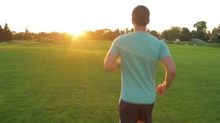 Morning run in the park. Guy runs on the evening meadow. Sports jogging outdoors. Running sports.