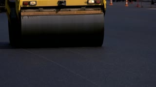 Motion of asphalt compactor. Dark road texture. Work oriented on quality. Fast construction of road.