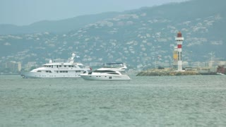 Motor yacht near lighthouse. Town on the hill. Travel to France by sea.